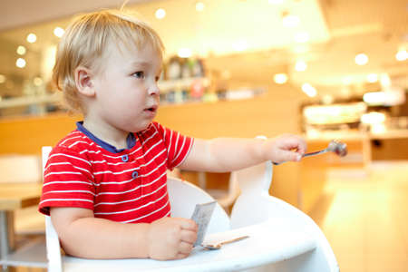 Little boy is sitting in the baby chair and holds the spoon in the restaurant  Stock Photo - 16637725