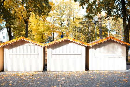 jurmala: Autumn landscape - three small wooden houses and yellow leaves in Jurmala, Latvia  Stock Photo