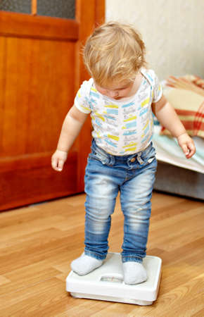Little boy is standing on the scales checking his weight Фото со стока - 16637724
