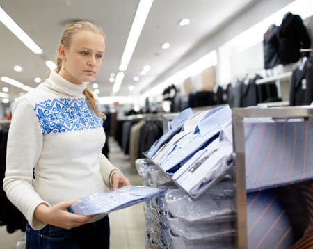 purchaser: Young woman is thinking what shirt will be the best for her boyfriend  Stock Photo