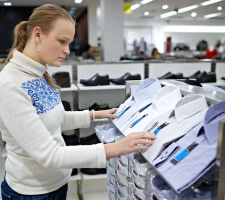 purchaser: Young woman is choosing a shirt for her boyfriend