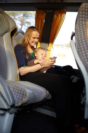 Young mother is playing games on the phone with her son, while travelling by bus  Stock Photo