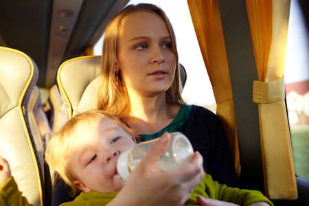 Young mother is feeding her two year old son with milk, while they are travelling by intercity bus  Close up portraits  photo