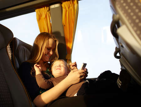 若い母親は遊んでゲーム電話で彼女の息子と笑っているバス男の子で旅行との彼の目をねじ込み 写真素材