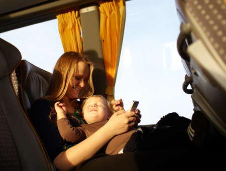 버스 보이로 여행 웃 고 그의 눈을 속이고있는 동안 젊은 어머니가 그녀의 아들과 함께 휴대 전화에 게임을 재생 스톡 콘텐츠
