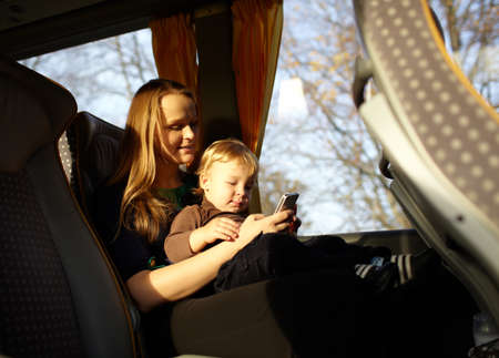 Young mother is playing games on the phone with her son, while travelling by bus  Beautiful natural light  photo