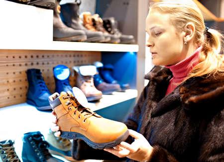 botas de navidad: Joven mujer caucásica es la elección de botas de invierno para los hombres s de su marido en una tienda de zapatos