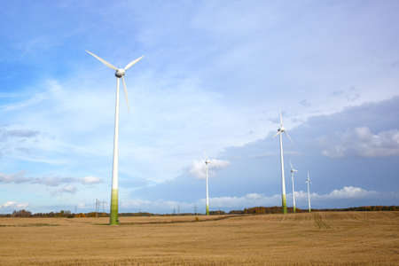Many wind turbines, green grass and blue sky with the clouds  Go green