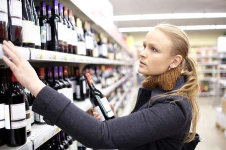 젊은 여성이 슈퍼마켓에서 와인을 선택하는 것입니다 스톡 콘텐츠
