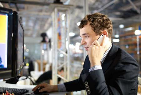 젊은 사람이 컴퓨터에서 작동 하 고 전화에 얘기