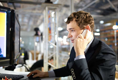 head support: The young man works at a computer and talking on the phone  Stock Photo