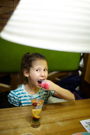 8 10 years: Eight year old girl is drinking coctail in the restaurant