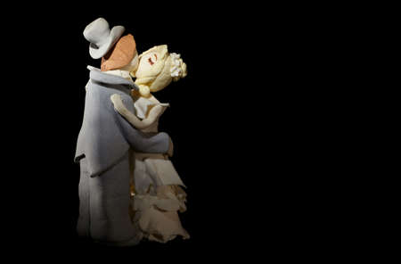 topper: Wedding cake figurines are kissing on black