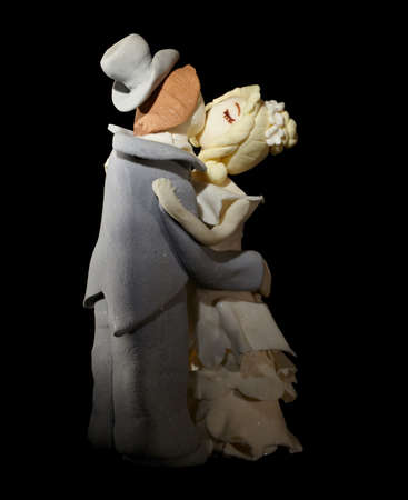 sugar veil: Wedding cake figurines are kissing on black