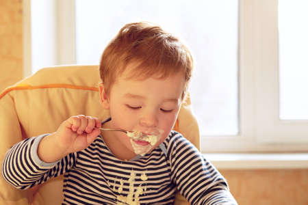 Portrait of two year old boy eating porridge in the morning  photo