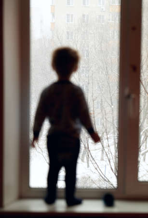 look through window: Boy stands on the windowsill and looking through the window  Stock Photo