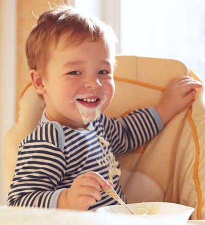 Two year old boy smiles to the camera eating porridge  Фото со стока