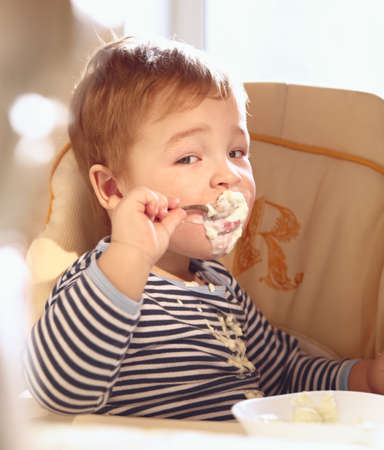 Portrait of two year old boy in the baby chair eating porridge in the morning  photo