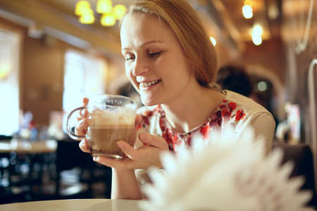 Portrait of girl enjoying coffee latte in cafe  Beautiful vintage interior in blur with natural sunlight  photo