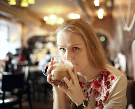 Portrait of girl enjoying coffee latte in cafe photo