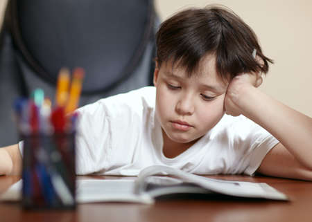 A teen school boy studies hard over his book at home as he props his head up with his arm  Stock Photo