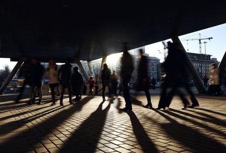 사람들은 지하철 역 근처에 산책. 백라이트 태양 도시 배경. 에디토리얼