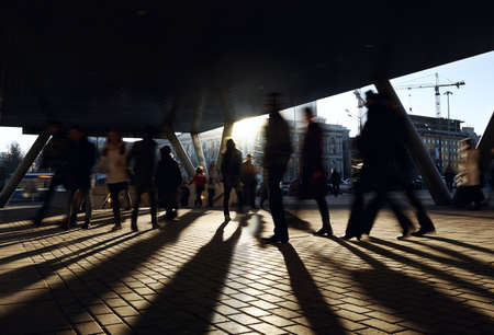 personas caminando: La gente que camina cerca de la estación de metro. Fondo de la ciudad con el sol de contraluz. Editorial