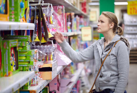 toy shop: Young woman is choosing toys for her kid  Middle shot