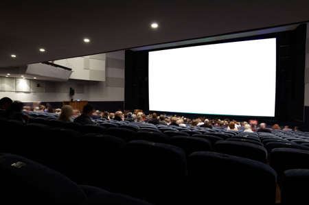 Cinema auditorium with people in chairs watching movie