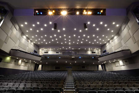 Interior of empty cinema auditorium with lines of chairs