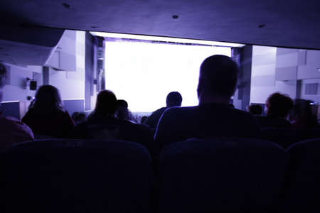 Group of people looking at clear white screen at cinema