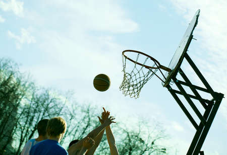 People playing basketball outdoors  Dynamic sport concept  No visible faces  Stock Photo