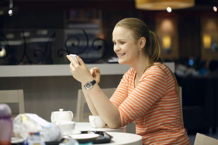 Young beautiful woman chatting on smartphone sitting in cafe photo