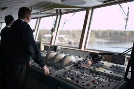 Navigation officer driving cruise liner on the river  Stok Fotoğraf