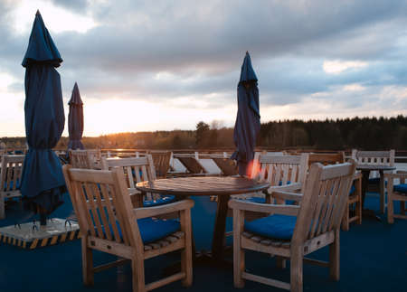 open air: Tables in outdoor bar on stern of cruise liner Stock Photo