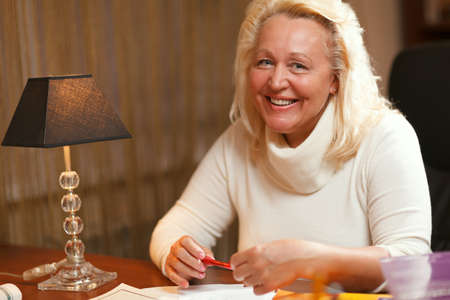 English teacher sitting at the table and smiling to the camera  Stock Photo - 20562045