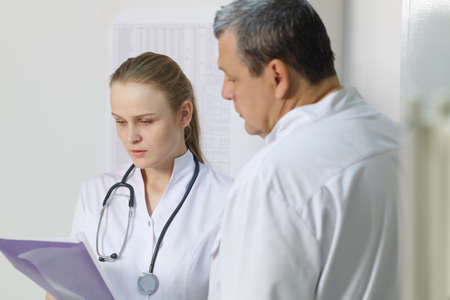 reported: The nurse reported to the doctor about medical tests  Close up
