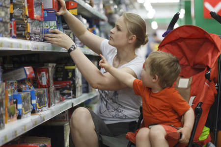 어머니와 그녀의 두 살짜리 아들이 장난감을 쇼핑하는