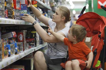 ni�os de compras: Madre y su hijo de dos a?os est? haciendo compras para los juguetes Foto de archivo