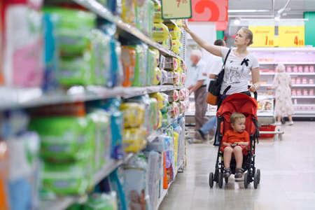Madre con su hijo en el cochecito de bebé en el supermercado