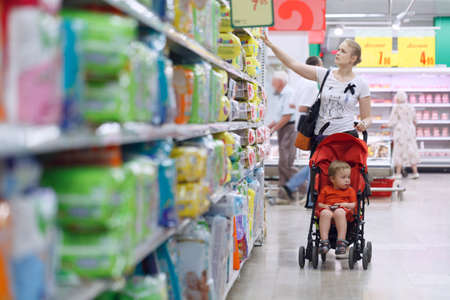 shopper: Mother with her boy in baby carriage in the supermarket