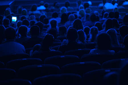 Audience in the cinema  Silhouette shot from back in blue light  報道画像