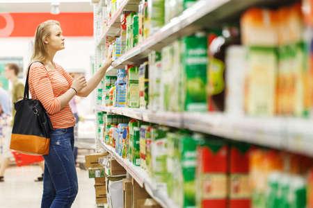 젊은 여자는 슈퍼마켓의 부서에서 주스를위한 쇼핑