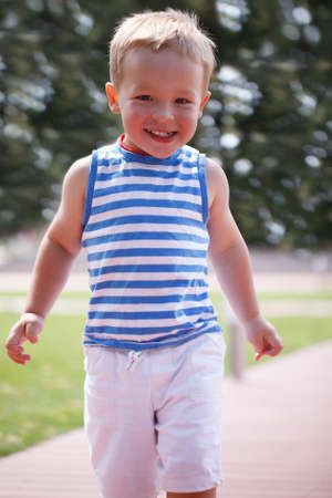 3 year old boy: Portrait of smiling happy 3 year old boy in striped vest running in the city park and looking to the photographer Stock Photo
