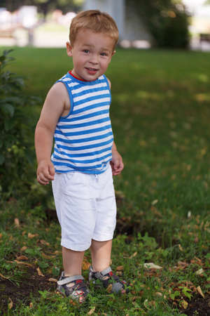 3 year old boy: Portrait of 3 year old boy in striped vest in the city park looking to the photographer and smiling Stock Photo