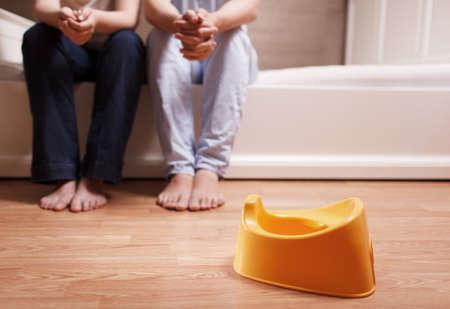 젊은 부모는 침대에 앉아 아이들의 냄비를 사용하는 아이를 가르 칠하는 방법을 생각하고있다. 필드의 얕은 깊이.