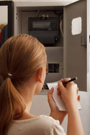 fusebox: Young woman rewrites the electrical meter readings at home in Russia Stock Photo