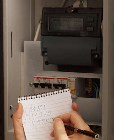 rewriting: Rewriting of the electrical meter readings at home in Russia. Close up shot.
