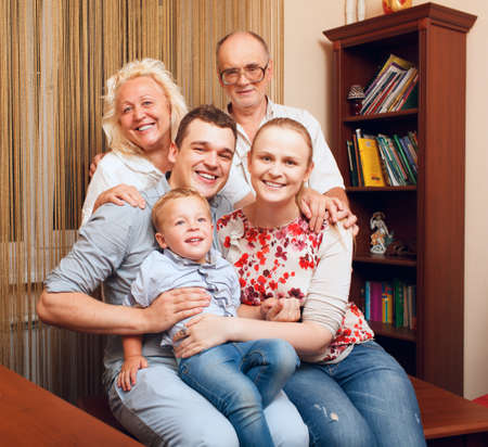large family portrait: Big happy family at home smiling and looking to the photographer. Generations - grandparents, parents and kid. Close up shot.