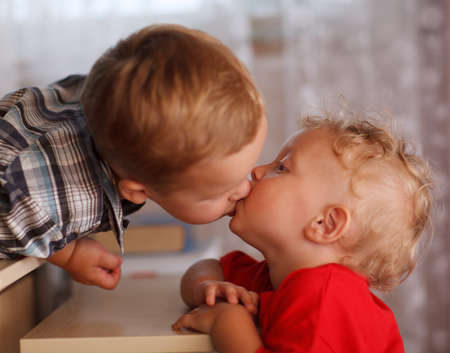 younger: Two little brothers are kissing. Close up portrait. Cute siblings.